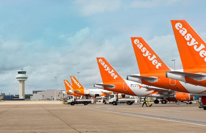 A row of Easy jet airplanes on the tarmac at an airport. The tail is visible. The control tower is in the background.