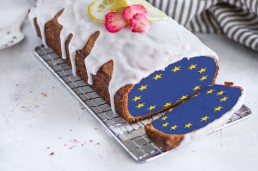 A loaf tin cake with white icing on the top. A slice has been cut from one end, the middle of the Brexit cake is coloured with the blue European flag.