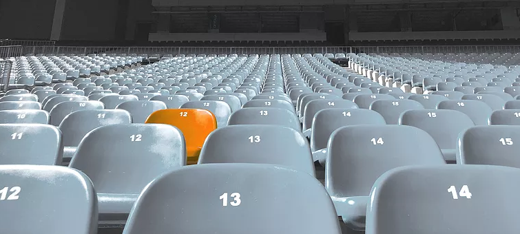 Stadium seating with one chair painted orange
